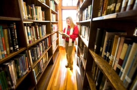 Sarah between bookshelves